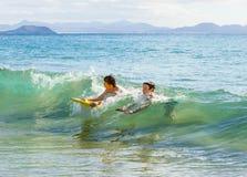 Två pojkar har gyckel i havet med deras boogiebräden Arkivbild