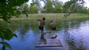 Två pojkar hoppar tillsammans till floden från pir stock video