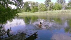 Två pojkar hoppar tillsammans till floden från pir lager videofilmer