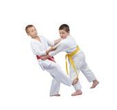 Två pojkar i judogi utbildar att skiva ner under benet Royaltyfri Fotografi