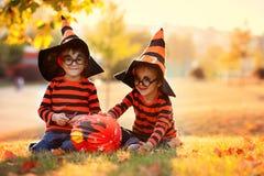 Två pojkar i parkera med allhelgonaaftondräkter Arkivfoton