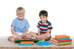 Två pojkar med böcker på golvet Royaltyfri Fotografi