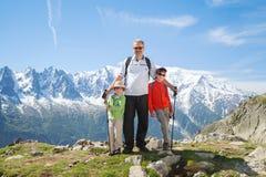 Två pojkar med farfadern på bergöverkanten arkivfoto