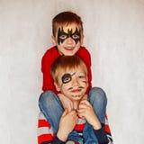 Två pojkar med framsidakonst av en hjälte och piratkopierar Ha deras framsidor Arkivfoton