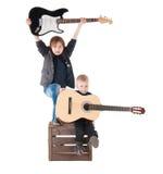Två pojkar med gitarrer på en ask Royaltyfri Bild
