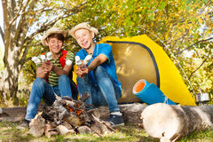 Två pojkar med pinnar för hatthållmarshmallow Fotografering för Bildbyråer