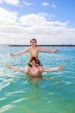 Två pojkar och brodern har gyckel i havet royaltyfria foton