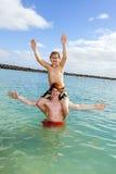 Två pojkar och brodern har gyckel i havet royaltyfri fotografi