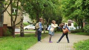Två pojkar och flickan går tillbaka hem efter skolan Hatten för flickaavverkningsugrör Pojken lyfter det Skolavänner stock video
