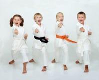 Två pojkar och två flickor slår stansmaskinarmen Royaltyfria Bilder
