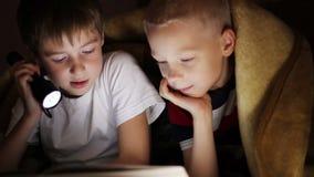 Två pojkar på natten under en filt som läser en bok