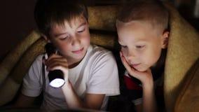 Två pojkar på natten under en filt som läser en bok stock video