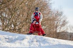 Två pojkar på pulkan på överkanten av den väntande på ridien för snöig kulle fotografering för bildbyråer