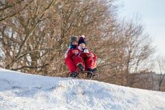 Två pojkar på pulkan på överkanten av den väntande på ridien för snöig kulle royaltyfria bilder