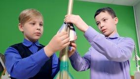 Två pojkar ser modellen av raket i klassrumet Steadicamskottet 4K stock video