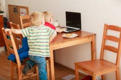 Två pojkar som använder bärbar datordatoren som spelar lekar Royaltyfria Foton