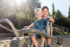 Två pojkar som använder grävaren på affärsföretaglekplats parkerar in Royaltyfri Bild