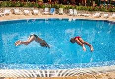 Två pojkar som dyker in i en pöl Arkivfoto
