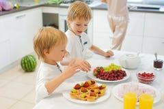 Två pojkar som förbereder frukosten i vitt kök Royaltyfri Foto