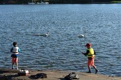 Två pojkar som fiskar från sjön arkivfoto