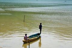 Två pojkar som fiskar i kricka och guling den färgade sjön i Nepal royaltyfri foto