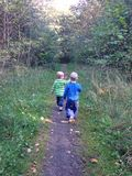 Två pojkar som går på en mest forrest bana Fotografering för Bildbyråer