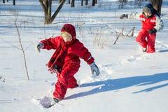 Två pojkar som går på snön parkerar på royaltyfria foton
