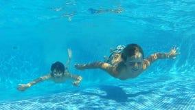Två pojkar som hoppar in i pöl simmar därefter, undervattens- till kameran stock video