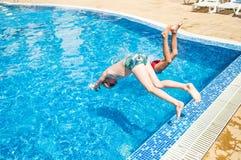 Två pojkar som hoppar in i simbassäng Royaltyfria Bilder