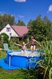 Två pojkar som hoppar och plaskar i simbassäng Royaltyfri Fotografi