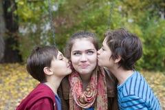 Två pojkar som kysser en tonårs- flicka Arkivfoto