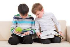 Två pojkar som läser den stora boken Royaltyfria Foton