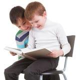 Två pojkar som läser den stora boken Arkivfoton
