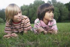 Två pojkar som ligger i äng arkivbild