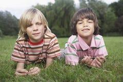 Två pojkar som ligger i äng arkivfoto