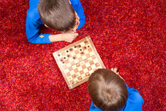 Två pojkar som ligger på golvet och spelar schack royaltyfria bilder