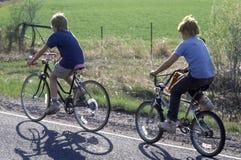Två pojkar som rider cyklar på den lantliga vägen, Arkivfoton