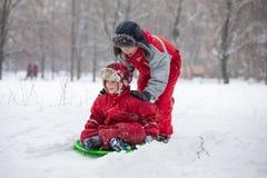 Två pojkar som rider på glidbanan på snöig, parkerar arkivbild