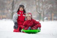 Två pojkar som rider på glidbanan på snöig, parkerar arkivfoton