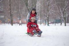 Två pojkar som rider på glidbanan på snöig stad royaltyfri foto