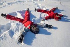 Två pojkar som sitter på snön parkerar på royaltyfri foto
