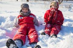 Två pojkar som sitter på snön parkerar på royaltyfri fotografi