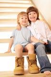 Två pojkar som sitter på trappa fotografering för bildbyråer