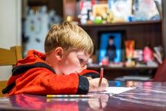 Två pojkar som skrivar brevet till Santa Claus på tabellen Royaltyfria Foton