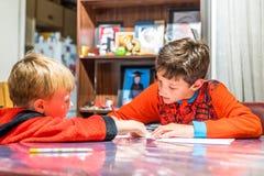 Två pojkar som skrivar brevet till Santa Claus på tabellen Fotografering för Bildbyråer