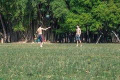 Två pojkar som spelar fotboll i eftermiddagen arkivbild