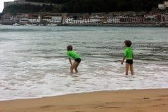 Två pojkar som spelar i vattnet arkivfoto