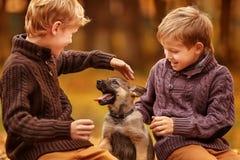 Två pojkar som spelar med en valp Royaltyfri Foto