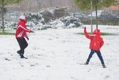 Två pojkar som spelar med, kastar snöboll royaltyfria foton