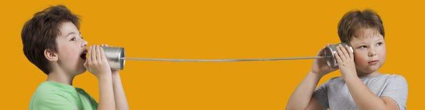 Två pojkar som spelar med Tin Can Phone Isolerat på orange bakgrund arkivbilder